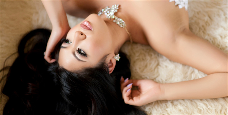 woman lays on a fur rug during boudoir photography session
