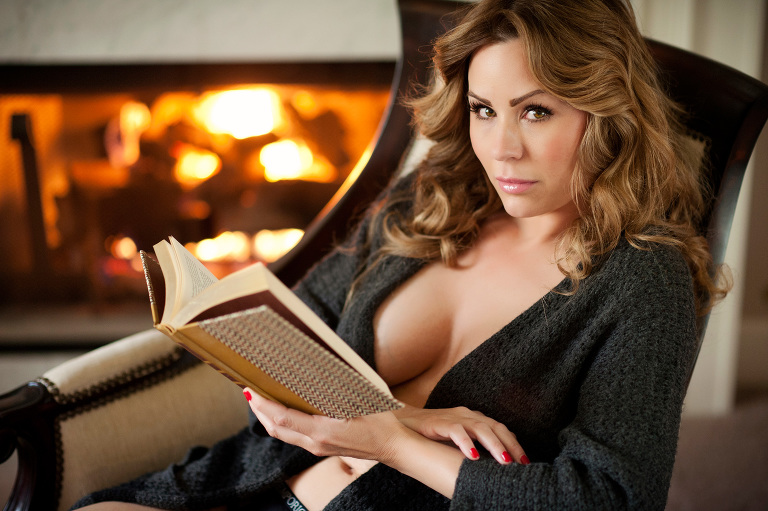 sexy girl reads by fireplace